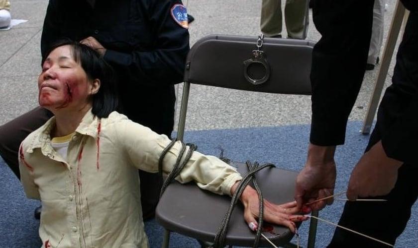 Reconstituição de tortura pela polícia em um centro de detenção. (Foto: Reprodução/Minghui.tv)