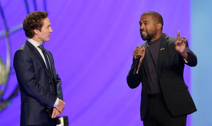 Kanye West ao lado do pastor Joel Osteen (à esquerda), durante um culto na Igreja Lakewood. (Foto: AP/Michael Wyke)