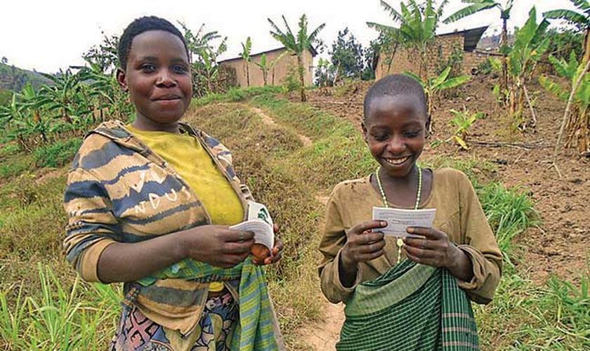 Meninas africanas recebem folhetos evangelísticos em seu idioma. (Foto: Reprodução/CHVN)