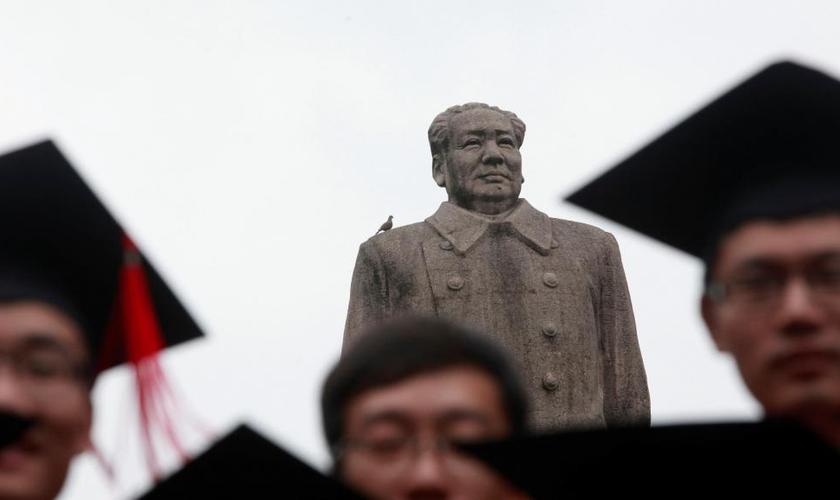 Graduados posam para foto em frente à estátua do líder chinês Mao Tsé Tung após sua cerimônia de formatura na Universidade de Fudan, em Xangai. (Foto: Aly Song/Reuters)
