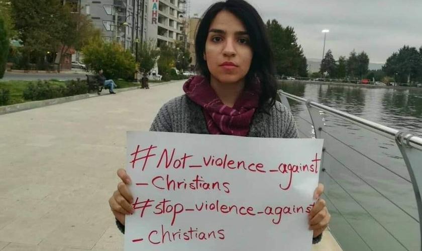 A ativista cristã Mary Fatemeh Mohammadi com placa contra perseguição aos cristãos. (Foto: Reprodução/Twitter)