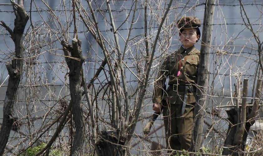 Policial norte-coreana guarda atrás de cercas em uma prisão às margens do rio Yalu. (Foto: Reprodução/Reuters)