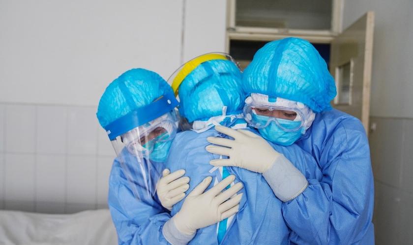 Membros da equipe médica se abraçando em uma ala de isolamento em um hospital em Zouping, no leste da China. (Foto: Stringer/AFP)
