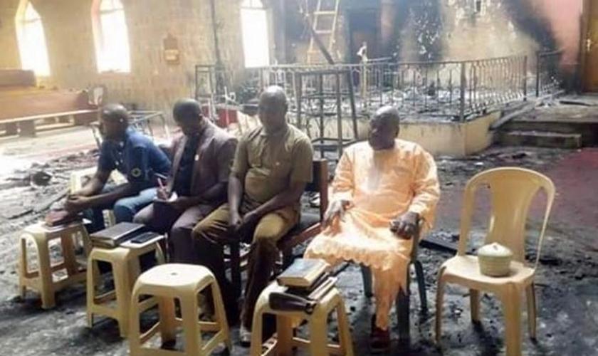 Os anciãos da igreja nigeriana realizam o culto de domingo em meio às cinzas de sua igreja incendiada apenas dois dias após um devastador ataque ao Boko Haram. (Foto: Reprodução / Barnabas)