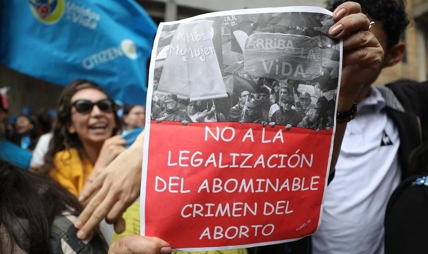 """Um ativista antiaborto segura uma placa que diz em espanhol """"Não à legalização do crime abominável do aborto"""", durante um protesto em frente ao tribunal constitucional da Colômbia em Bogotá, em 2 de março. (Foto: Fernando Vergara / AP)"""
