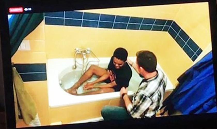 Akille sendo batizado na banheira de sua casa pelo pastor Reid Karr. (Foto: Reprodução/IMB)