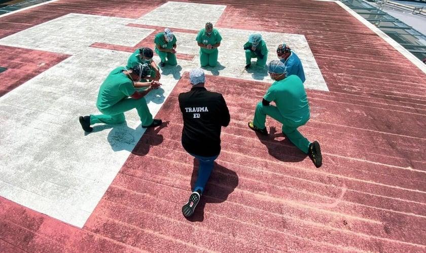 Funcionários do Jackson South Medical Center, na Flórida, oram no heliporto do hospital. (Foto: Jackson Health System)