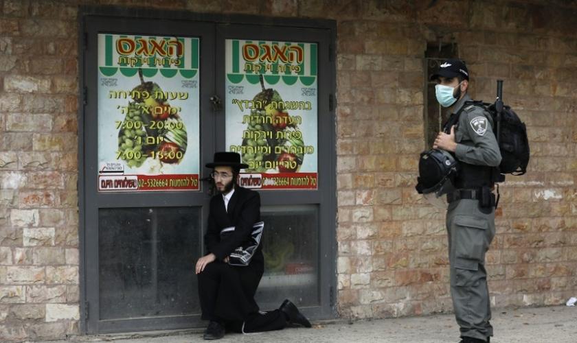 Policial israelense detém um judeu ultraortodoxo durante patrulha em Jerusalém. (Foto: Reprodução/AFP)