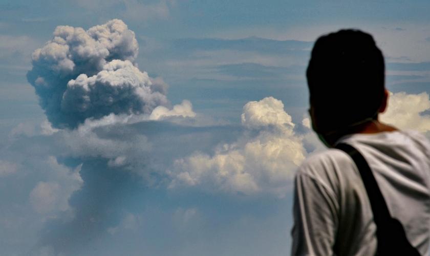 Homem observa fumaça do vulcão Krakatoa em erupção na Indonésia. (Foto: Ronald Siagian/AFP)