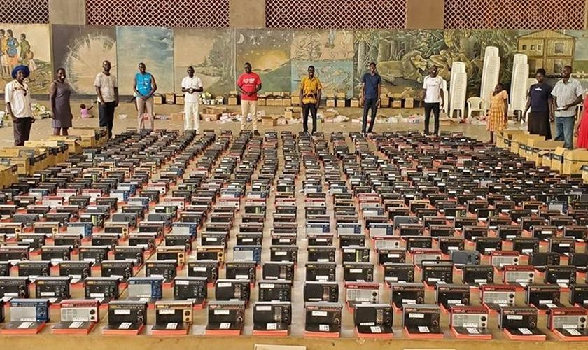 Uma equipe da Fundação Irene Gleeson, em Uganda, ora diante de Bíblias, rádios transistorizados que devem ser distribuídos a 1000 famílias nos distritos de Kitgum e Lamwo. (Foto: Reprodução/UGCN).