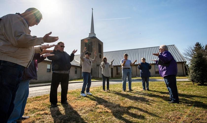 Cristãos oram do lado de fora da igreja. (Foto: Paul Kuehnel/USA Today)