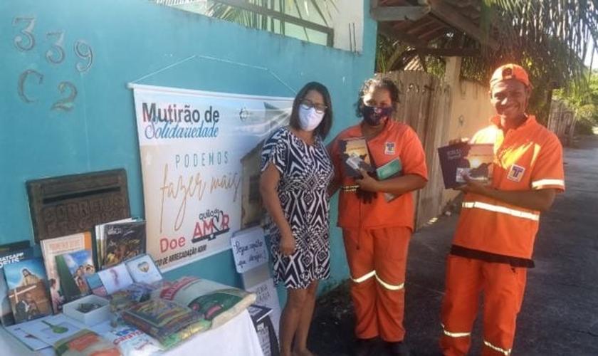 A mesa solidária despertou a atenção de dois profissionais de limpeza urbana que quiseram pegar livros religiosos. (Foto: Arquivo pessoal)