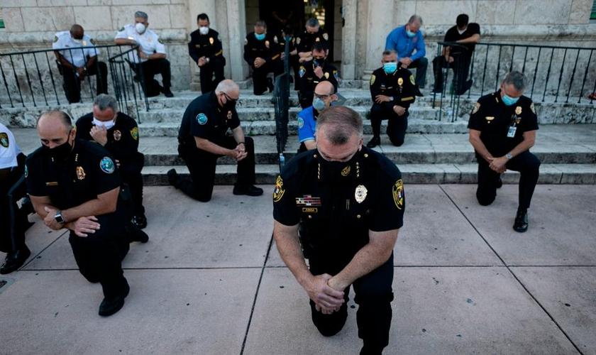 Policiais se ajoelharam durante um comício em Coral Gables, Flórida, no sábado, em resposta à morte de George Flay. (Foto: Eva Marie Uzcategui / AFP via Getty Images)