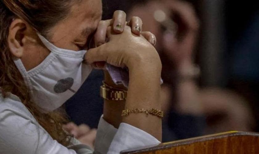 Cristã chinesa ora em meio à pandemia de coronavírus. (Foto: Reprodução/Barnabas Fund)