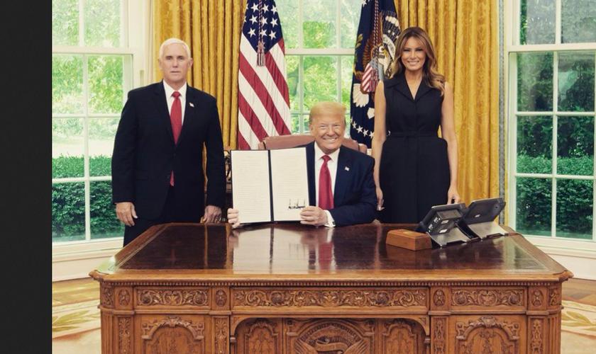 Donald Trump exibe a assinatura da ordem, entre a primeira-dama Melania e o vice Mike Pence. (Foto: Reprodução/Twitter)