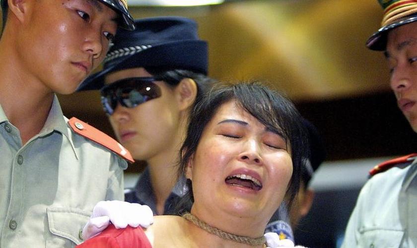 Mulher presa pela polícia comunista chinesa. (Foto: Reprodução/The Epoch Times/Getty)