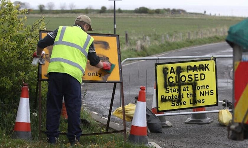 Trabalhador remove suástica pintada em uma placa na entrada de uma estrada fechada e parque de estacionamento perto do farol de Whitley Bay, em Northumberland, Inglaterra, quinta-feira, 30 de abril de 2020. (Foto: Owen Humphreys / AP)