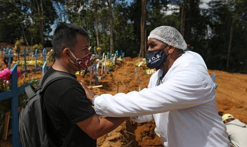 O pastor Izaías Nascimento conforta um jovem durante o funeral de seu pai. (Foto: Michael Dantas/AFP)