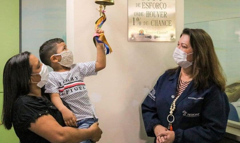 Brener Lorenzo, de 4 anos, toca o sino da cura após dois anos e meio de tratamento. (Foto: Governo do Amazonas)