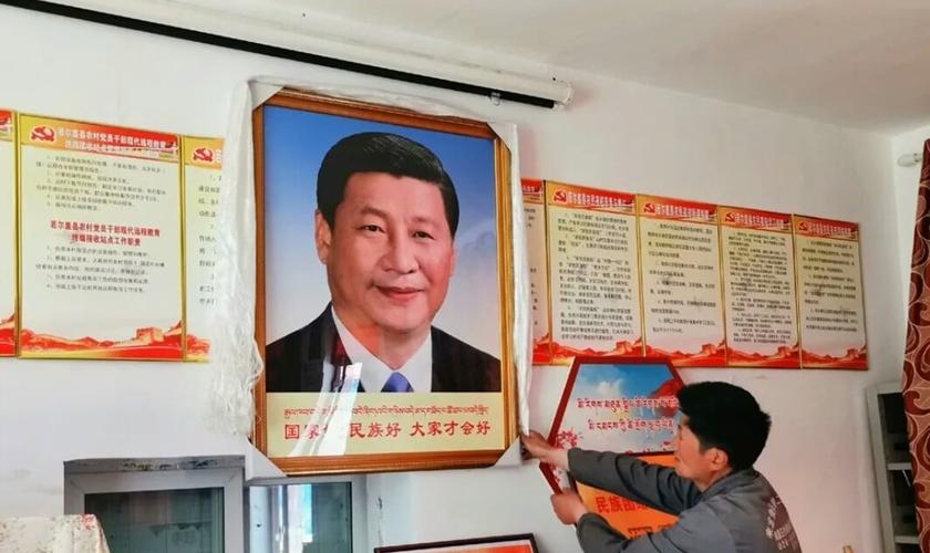 Homem pendura um retrato do presidente chinês Xi Jinping, no condado de Dzoge, no leste do Tibete. (Foto: Free Tibet)