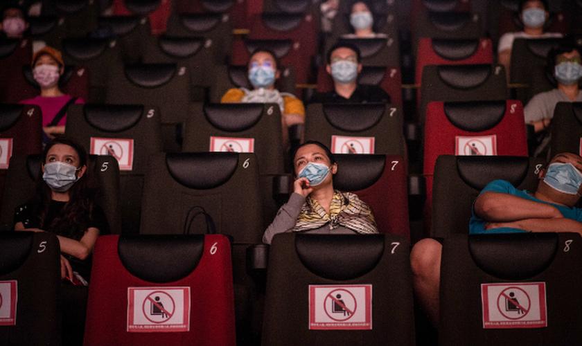 As pessoas assistem a um filme no dia 20 de julho, no primeiro dia da reabertura dos cinemas chineses em Wuhan, na província de Hubei. (Foto: Reprodução / AFP)