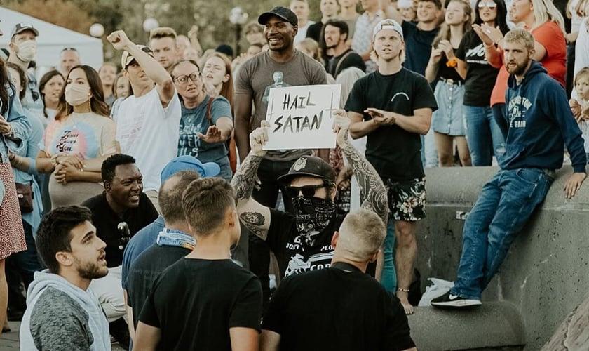 """Homem segura placa com a frase """"Salve Satanás"""" em meio a cristãos em Seattle. (Foto: Instagram/Sean Feucht)"""