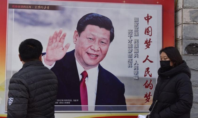 Pessoas passam por um pôster do presidente chinês Xi Jinping ao lado de uma rua em Pequim. O controle cada vez maior de Xi Jinping sobre a China já rendeu ao líder comparações com Mao Tsé Tung. (Foto: AFP / GREG BAKER)