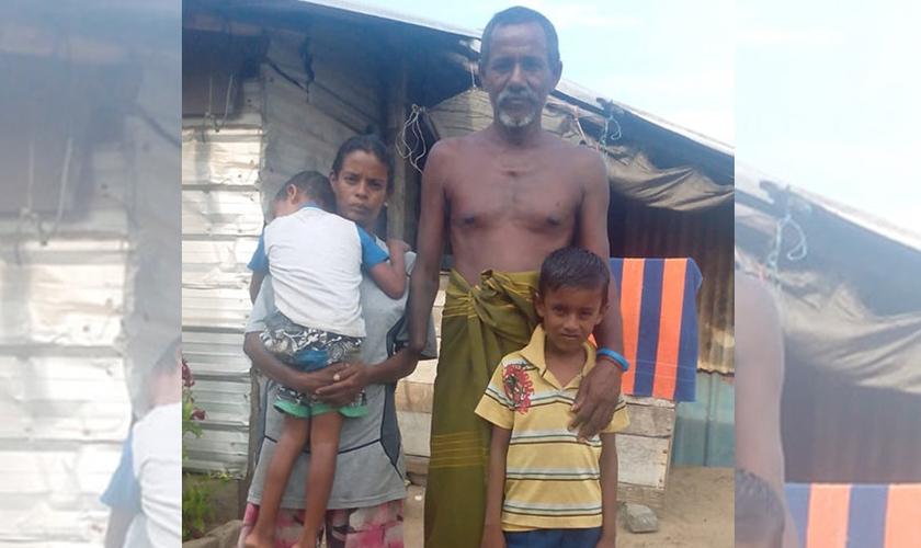 Khanjana ao lado da esposa e dois filhos, em frente à cabana da família. (Foto: Gospel For Asia)