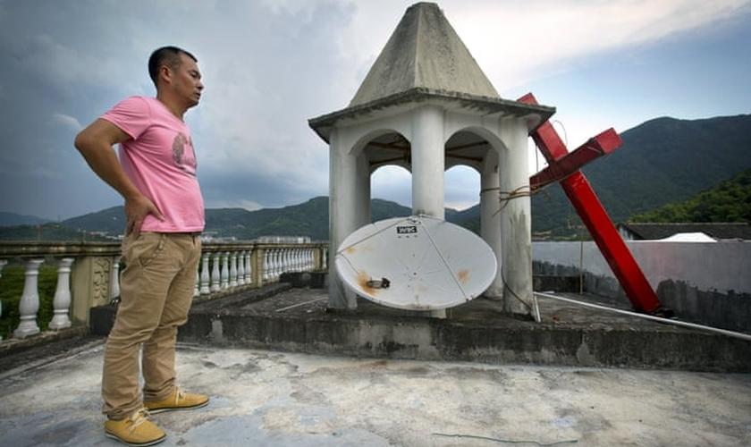 Líder de igreja permanece em pé no teto do templo, após o local ter sua cruz removida, na província de Zhejiang. (Foto:  Mark Schiefelbein/AP)