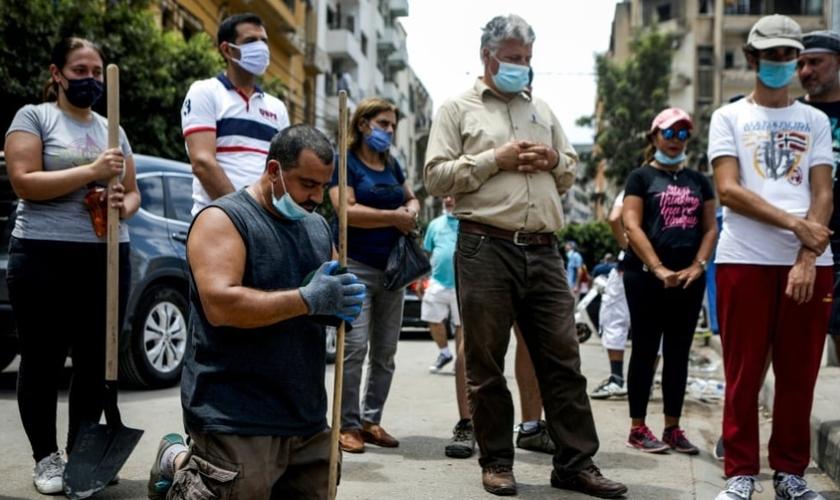 Voluntários se unem em mutirão para limpeza das ruas de Beirute e param para orar pelo Líbano. (Foto: AFP)