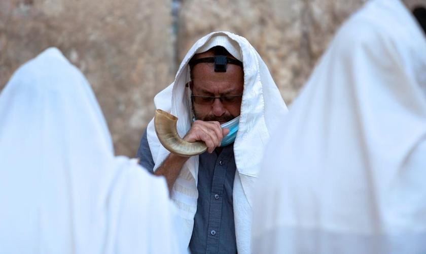 Um judeu ultraortodoxo toca um shofar, um instrumento musical feito de chifre de animal, enquanto ora antes do ano novo judaico no Muro das Lamentações. (Foto: AP Photo / Sebastian Scheiner)