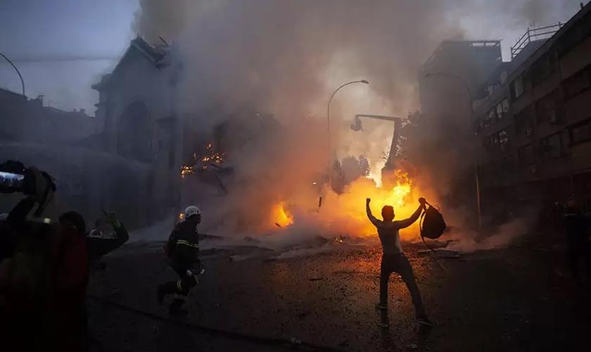 Homem comemora em frente a igreja destruída em Santiago. (Foto: Claudio Reyes / AFP)