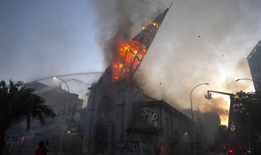 Igreja em chamas após ataque de manifestantes encapuzados em Santiago, no Chile. (Foto: AFP/Martin Bernetti)
