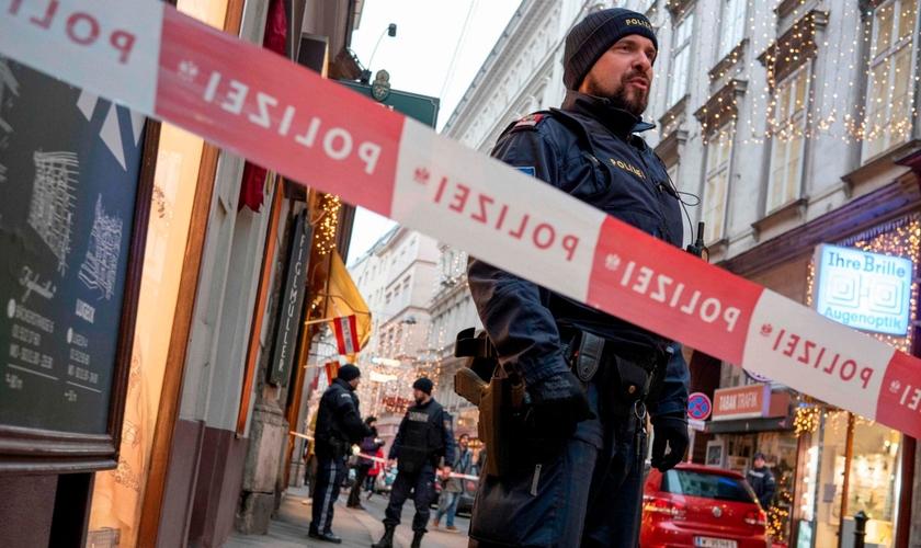 Policial austríaco permanece próximo a cordão de isolamento, em uma das cenas do ataque terrorista em Viena. (Foto: AFP)