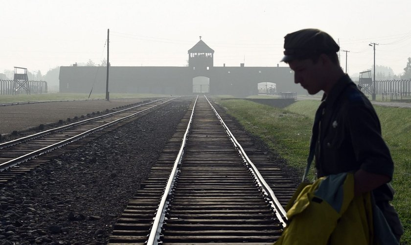 Homem atravessa trilhos do antigo campo de concentração de Auschwitz, na Polônia. (Foto: AP/Alik Keplicz)