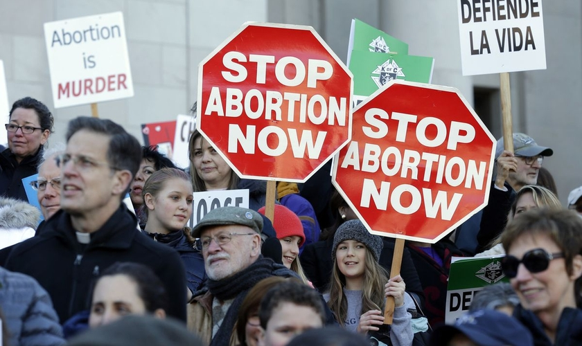 """Manifestantes pró-vida protestam contra o aborto, segurando cartazes que dizem """"Parem o Aborto Agora"""", enquanto ouvem os palestrantes em 23 de janeiro de 2017, no Capitólio em Olympia. (Foto: AP / Ted S. Warren)"""