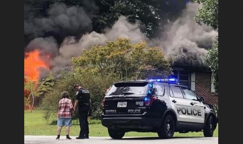 Sem perceber, policial é fotografado orando com mulher que perdeu casa em incêndio. (Foto: Reprodução / Facebook)