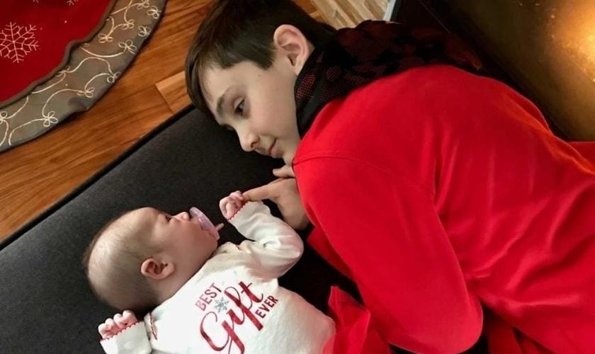 Owynn se deita ao lado da irmã mais nova, após vivenciar a emoção de ver suas orações atendidas. (Foto: Facebook)
