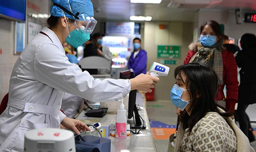 Profissional de saúde checa temperatura de mulher em um hospital de Fuzhou, na China. (Foto: Xinhua)