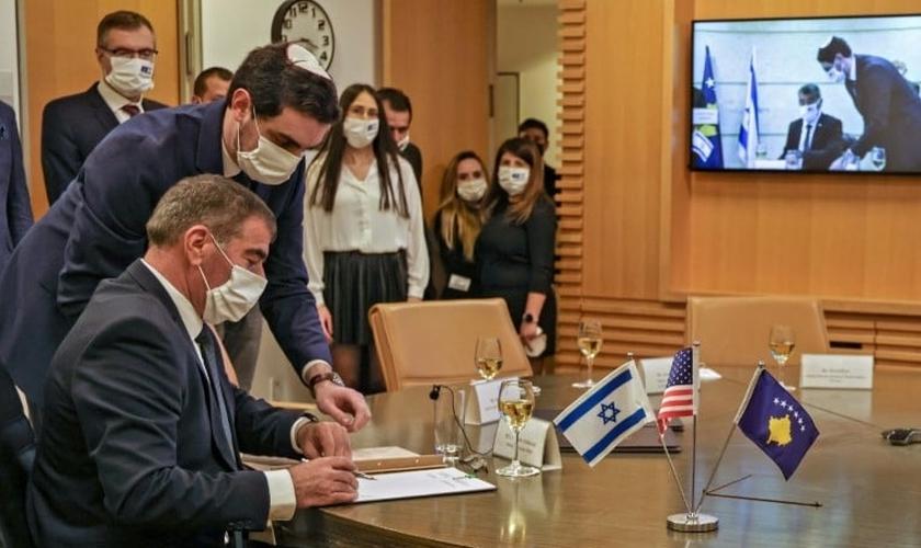 O ministro israelense das Relações Exteriores Gabi Ashkenazi assina documento de normalização das relações diplomáticas com Kosovo. (Foto: Reprodução / AFP)