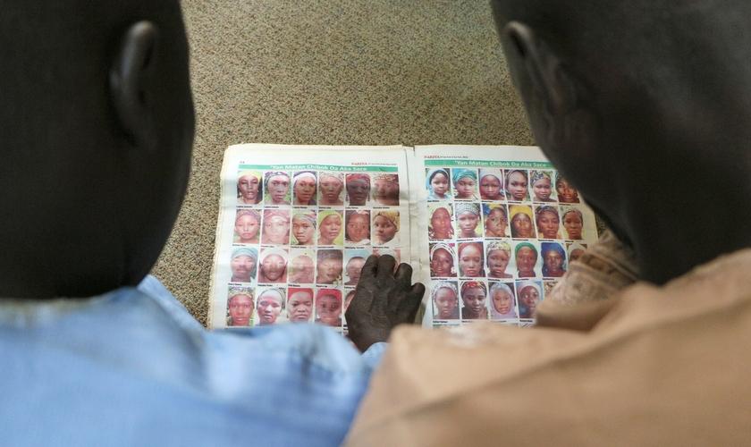 Dois pais de meninas Chibok olham retratos de algumas das meninas sequestradas por Boko Haram em 2014. (Foto: Reprodução / Portas Abertas UK)