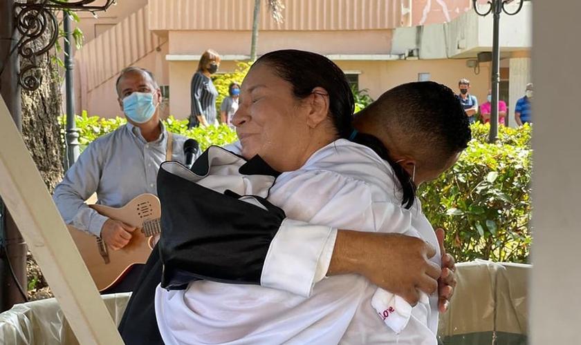 Maritza Tillero e o pastor Roberto Viscaíno se abraçam após o batismo em 20 de janeiro de 2021. (Foto: Hospital Bella Vista)