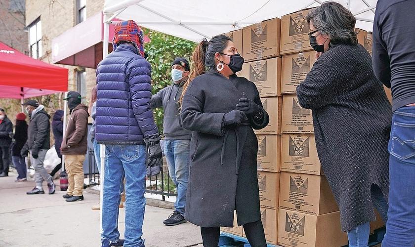 A voluntária Gloria Martinez, à esquerda, fala com Sofia Moncayo, que dirige um programa de distribuição de alimentos por meio da Mosaic West Queens Church. (Foto: Emily Leshner / AP)