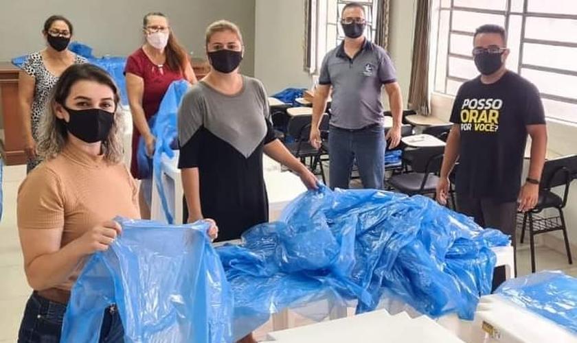 A equipe da AD dobra, empacota e organiza os aventais individualmente e que após são enviados às equipes do hospital. (Foto: Divulgação/AD Chapecó).