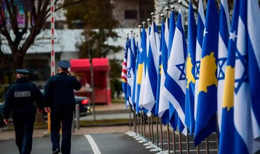 Policiais passam por bandeiras de Kosovo e Israel expostas durante uma cerimônia em Pristina em fevereiro, depois que os países estabeleceram relações diplomáticas. (Foto: Armend Nimani / AFP / Getty Images)