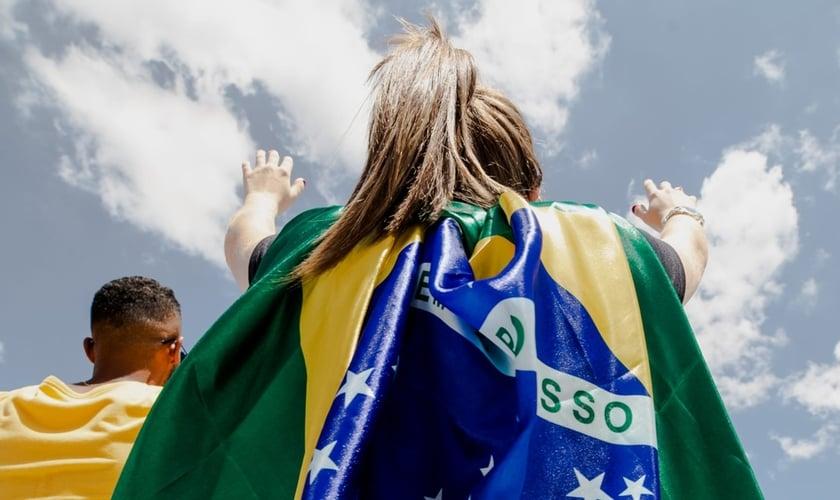 Jovem com bandeira do Brasil em momento de oração, em 8 de fevereiro de 2020. (Foto: The Send Brasil)
