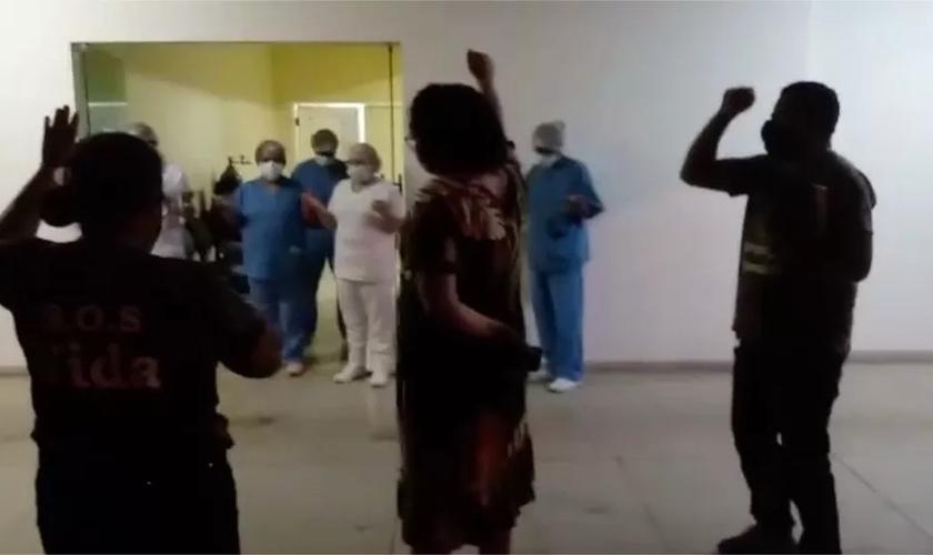 Parente de pacientes e profissionais de saúde oram na frente do Hospital Regional de Augustinópolis. (Foto: Reprodução / G1)