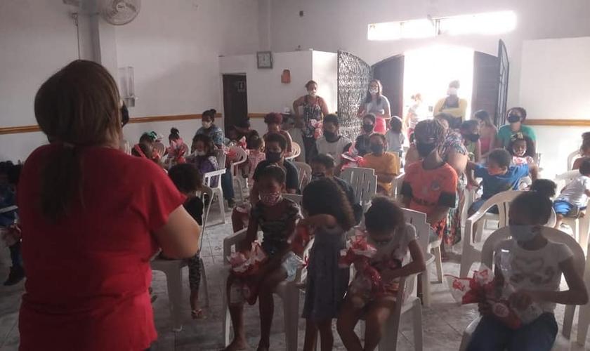 A diretora Dilene Santos ora com as crianças do Projeto Kids Crescer e Vencer. (Foto: Reprodução / Facebook)
