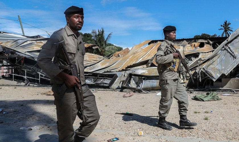 Soldados do exército moçambicano passam por um prédio destruído por insurgentes ligados ao Estado Islâmico em Palma, Moçambique. (Foto: João Relvas/EPA/Shutterstock)