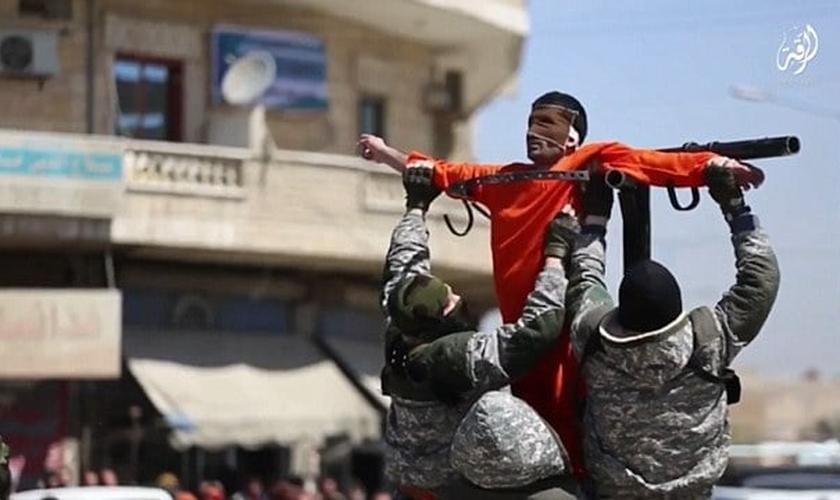 Com o rosto vendado, homem é crucificado por dois carrascos do Estado Islâmico. (Foto: Reprodução/Daily Mail)